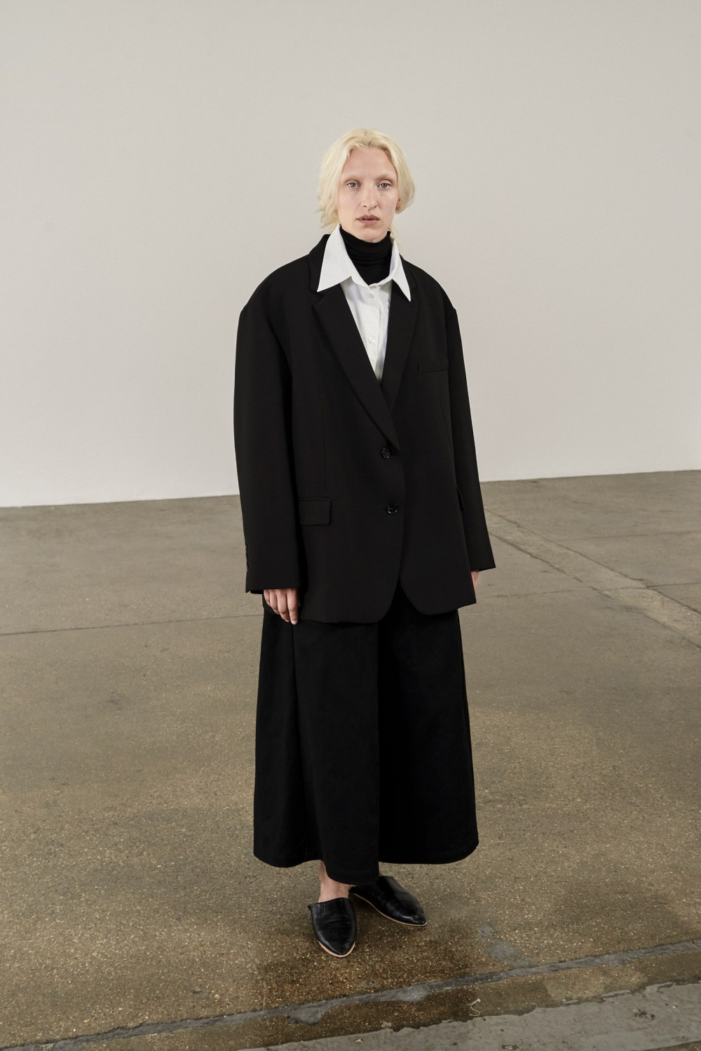 Image may contain Clothing Apparel Suit Coat Overcoat Tuxedo Dress Human Person Female Footwear and Shoe