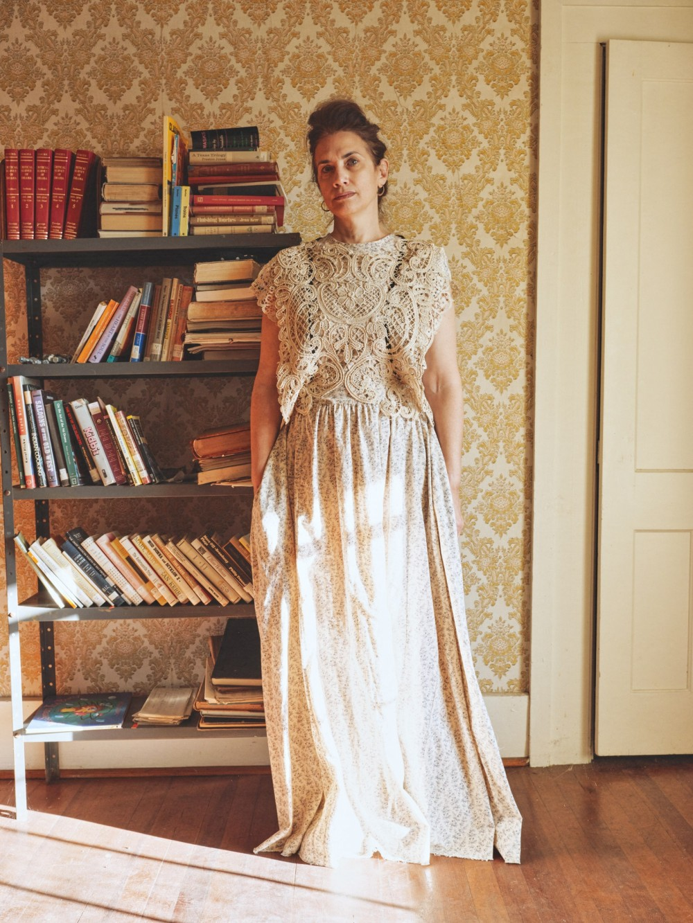 Image may contain Furniture Shelf Bookcase Human Person Clothing Apparel Evening Dress Fashion Gown Robe and Wood